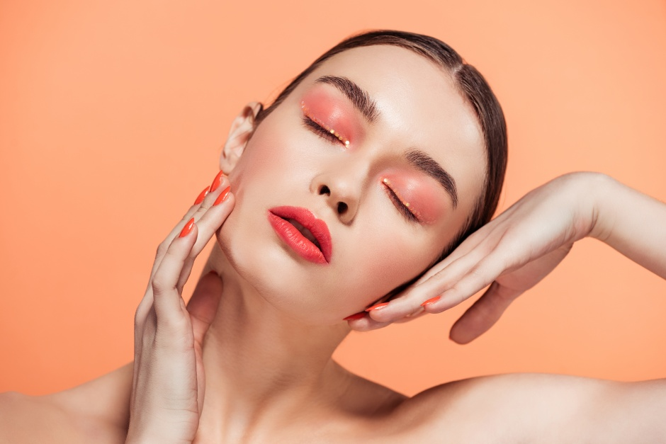 beautiful stylish young woman with glitter makeup posing isolated on coral